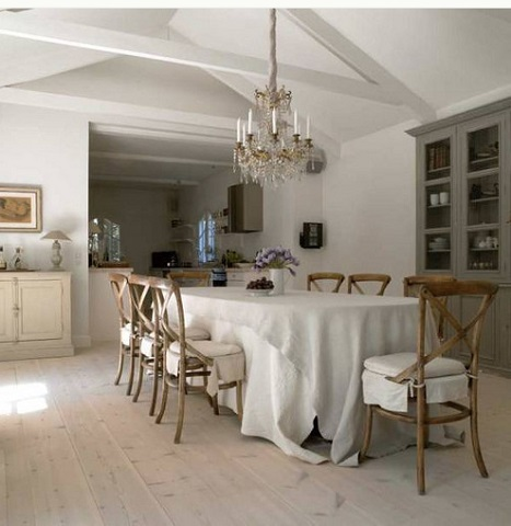 Pairing Rustic Cross Backed Dining Chairs With Crisp White Liniens And An Antique Chandelier Creates a Look That's Both Inviting And Sophisticated (by Margaret Everton)