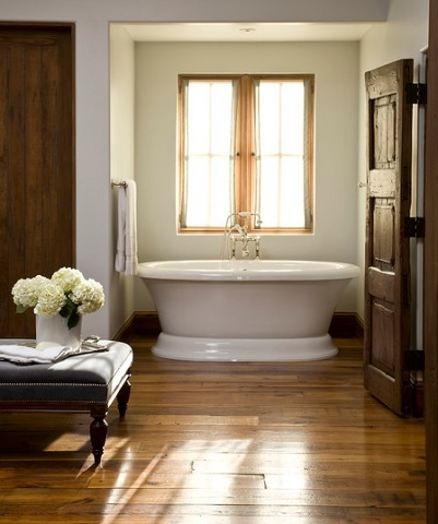 Natural wood floors have beautiful warmth, texture, and natural character, but require vigilant upkeep in a wet space like a bathroom (by Palm Design Group)