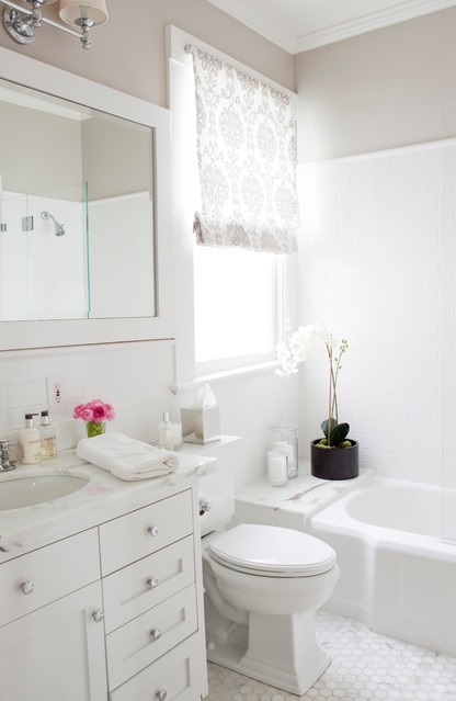 Placing toiletries in a few nice containers - deluxe soap and lotion, cotton swabs in glass jars, and so on - will give the bathroom a more polished look. Add cut flowers or a small live plant for an extra fresh, finished look (by Caitlin Wilson)