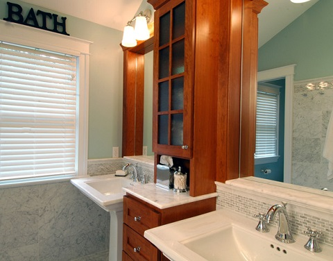Pairing two pedestal sinks with a central storage cabinet is a classic twist on the conventional double vanity, and can make the bathroom feel larger and more open (by Case Design Remodeling Inc.)