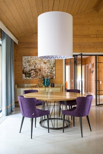 If you want to add an eye-catching pop of color that's a little more permanent than a throw pillow, consider dressing up your space with a purple chair or two (by TS Design)